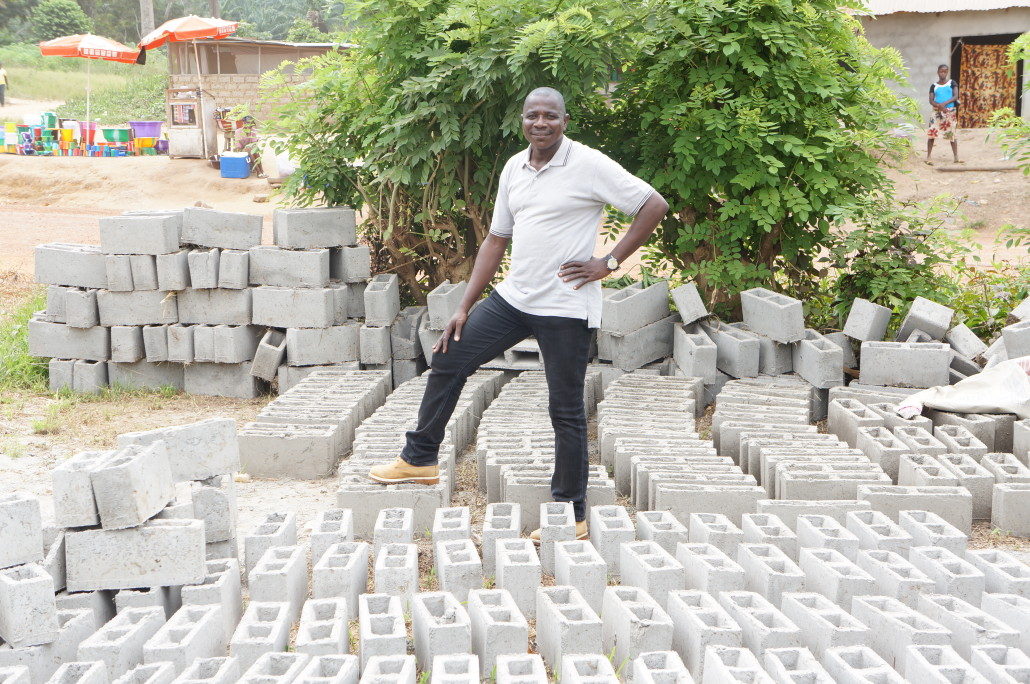 Mr. Yangean standing infront of cement blocks made to complete the caretaker's facility